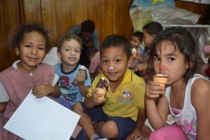 Na frente, alguns alunos posam para a foto. Atrás, Edu interage com outras crianças.